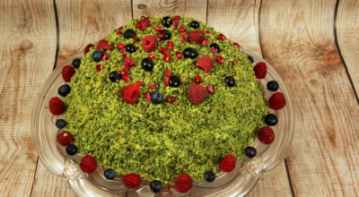 Spinach cake layered with mascarpone cheese and crumble dough imitation moss, decorated with fruits of the forest, on wooden deskach.Horizontal view.