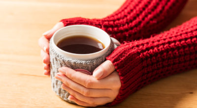 Hot mug of tea warming woman's hands in retro woollen jumper. Wooden table